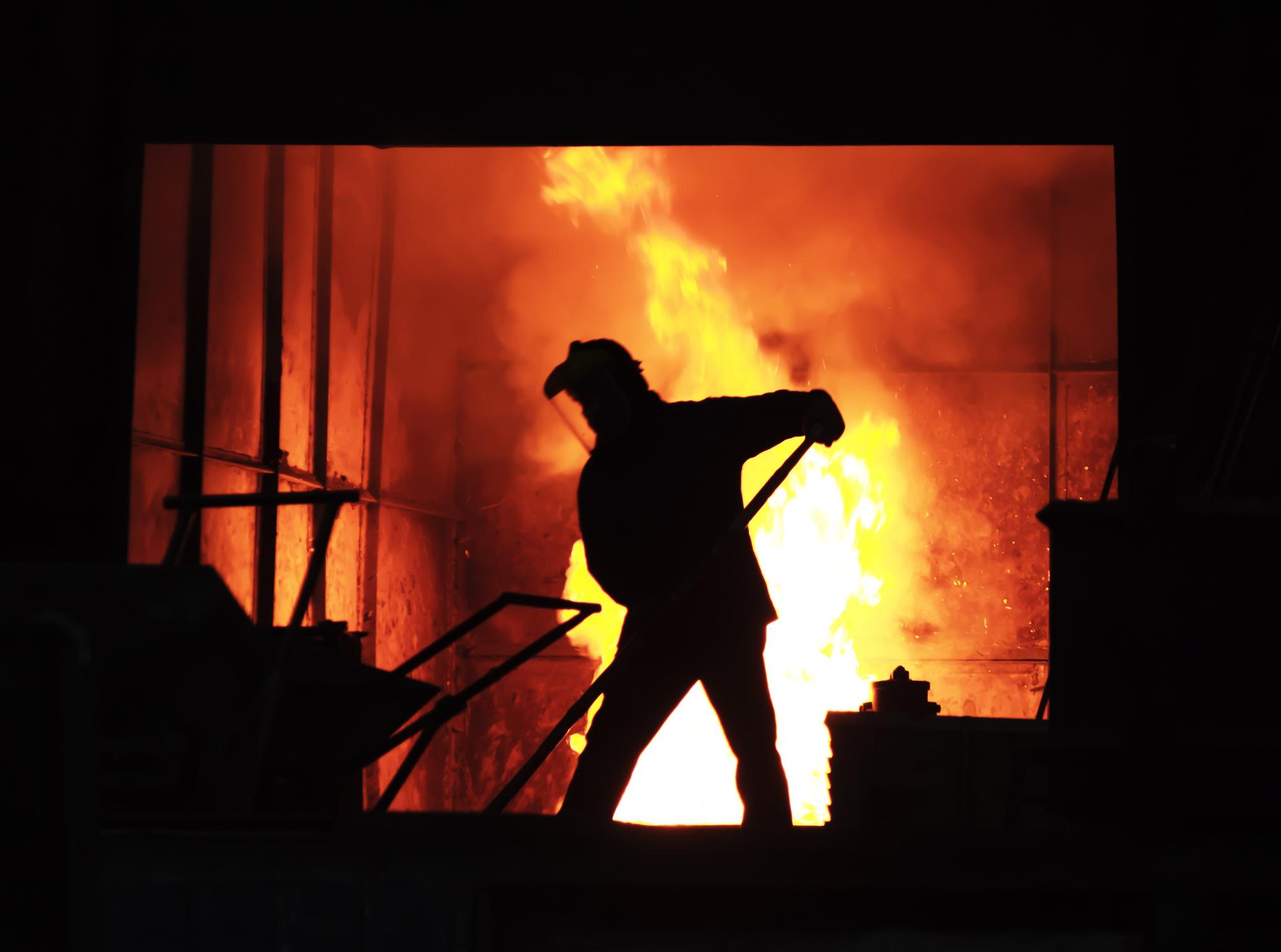 man working with molten iron