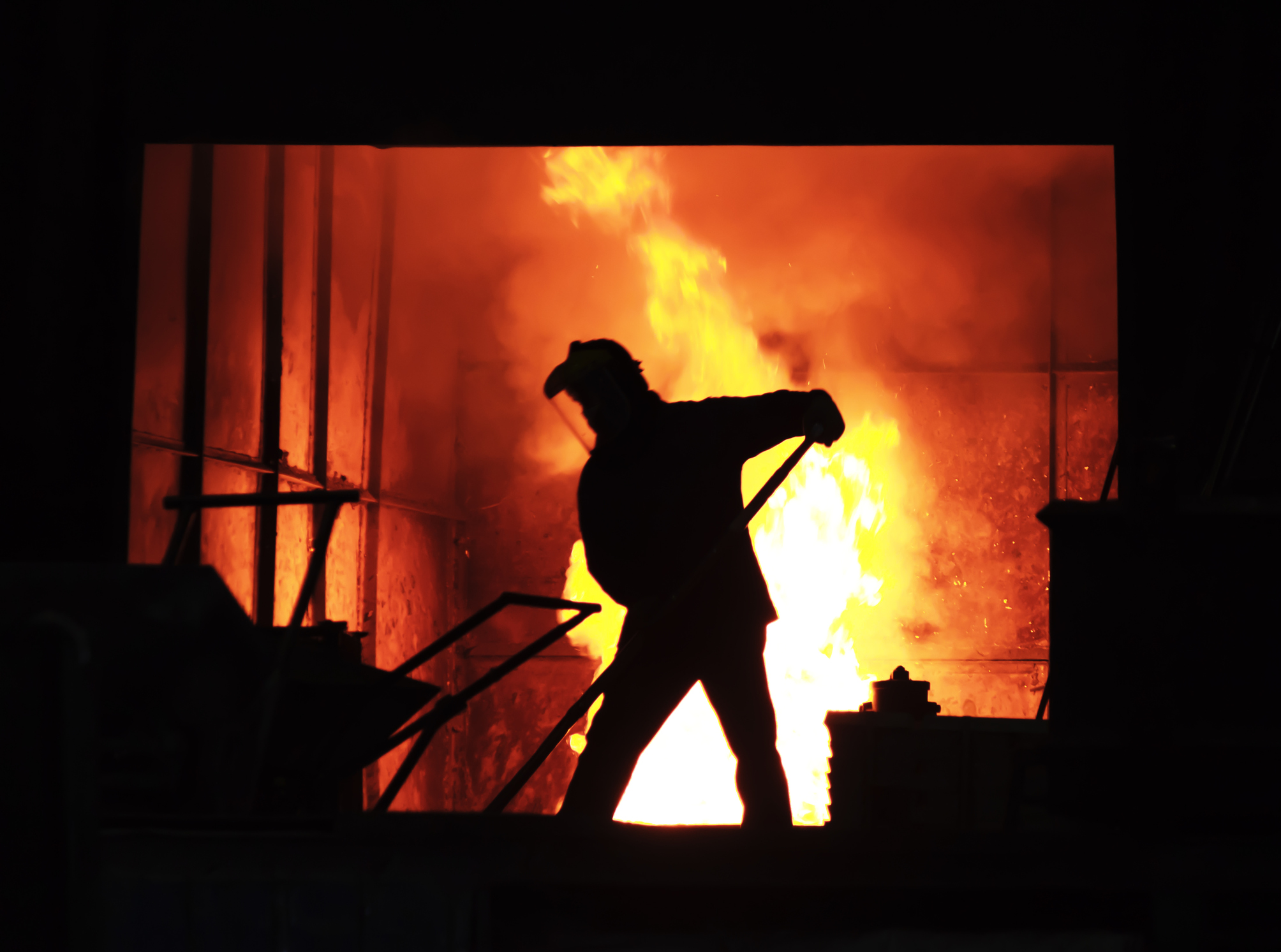 man working with molten iron