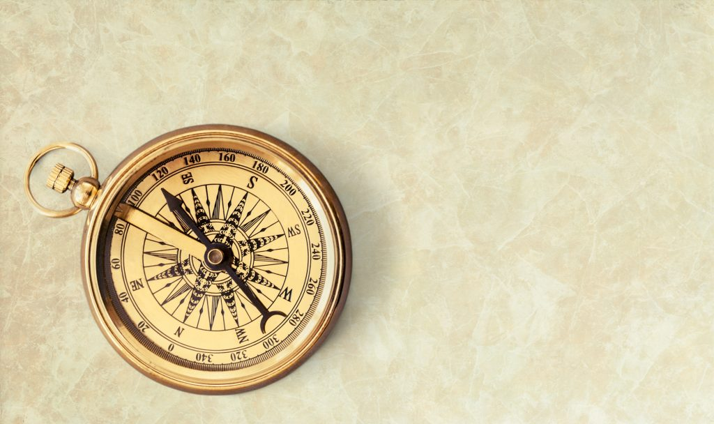 Brass antique compass on beige background