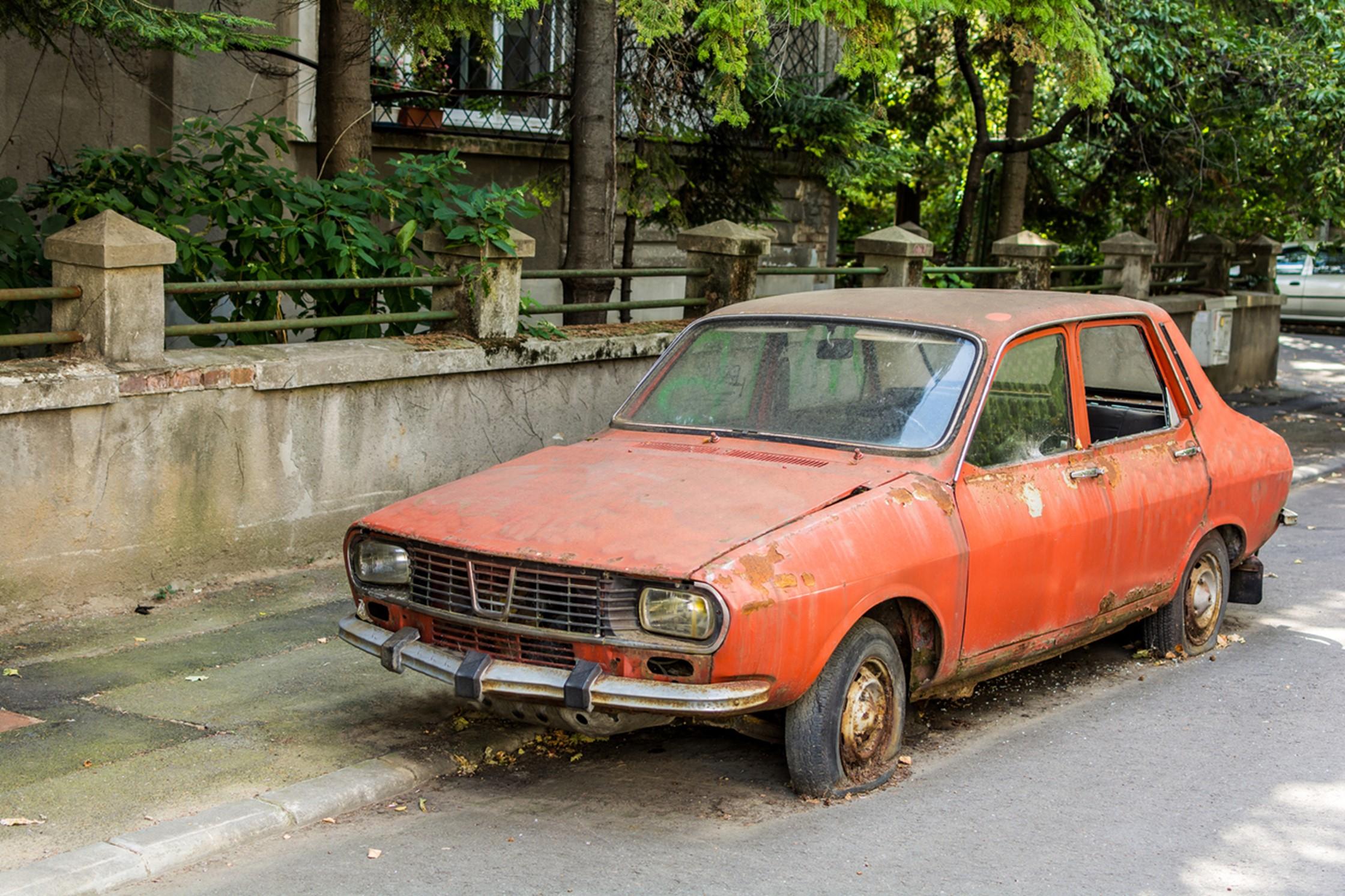 scrap orange car on a road